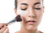 oříznutý obraz vizážistiku dělá make-up pro mladou ženu s pudr izolované na bílém
