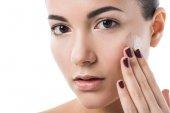 atraktivní dívka použitím nadace krém na tvář a při pohledu na fotoaparát izolované na bílém