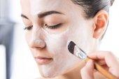 oříznutý obraz kosmetičky použitím krém na obličej dívky izolované na bílém