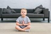 Malý chlapec praktikování jógy v lotosové pozici v obývacím pokoji