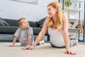 Šťastný matka a syn cvičí jógu v moderním obývacím pokoji