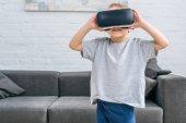 Kleiner Junge mit virtual-Reality-Kopfhörer vor sofa