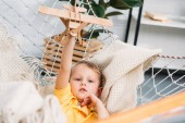 Photo Happy boy playing with wooden airplane toy in hammock