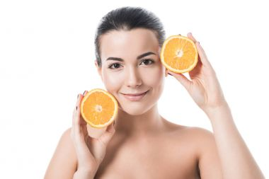 Attractive smiling naked girl with clean skin holding orange pieces isolated on white stock vector