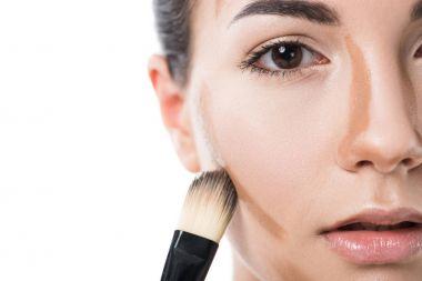 cropped image of beautiful girl applying foundation cream with brush isolated on white
