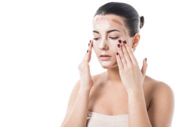 beautiful girl applying foundation cream on face isolated on white