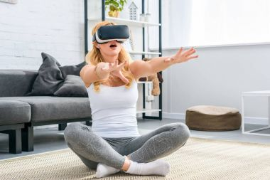 Young woman sitting and using virtual reality headset