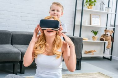 Mother using virtual reality headset with little son standing behind