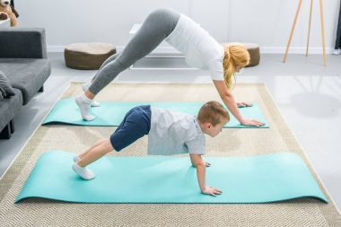 Side view of mother and little son in adho mukha svanasana position on yoga mats