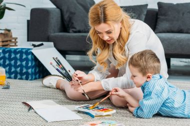 Young mother and little son painting together