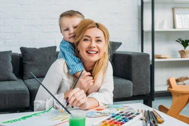 Little son embracing smiling mother while she painting at home