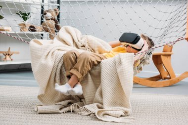Little boy laying in rope hammock and using virtual reality headset