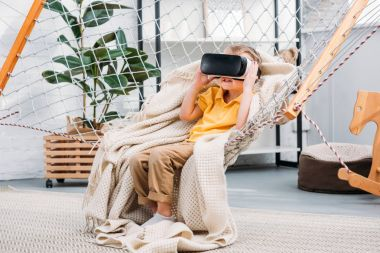 Boy in rope hammock using virtual reality headset