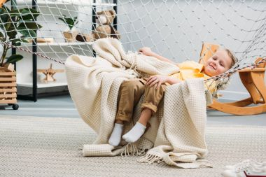 Smiling little boy laying in rope hammock