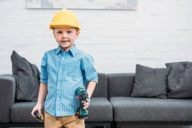 Little boy in safety helmet with toy drill pretending to be workman