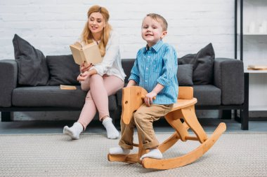 Mother reading book to son while he riding rocking horse