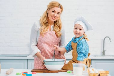 Mother and little son in kitchen cooking together