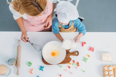 Top view of mother and boy pouring milk into bowl with egg and flour