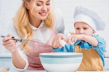 Mother with hand beater and little boy pouring egg into bowl