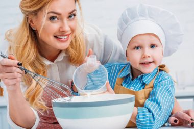 Happy mother with hand beater and little boy pouring milk into bowl