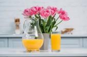 Elölnézet a narancslé és a rózsaszín tulipánok a vázában a modern konyha asztal