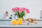 Fotografie Pink tulips in vase, orange juice and wooden airplane on table in modern kitchen