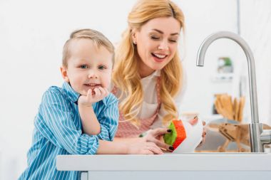 Little boy and mother washing up plate by sponge