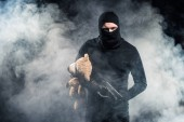 Fotografie Criminal in balaclava holding gun and teddy bear in clouds of smoke