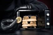 Oříznutý pohled zloděj krade gold bullions a bitcoin z bezpečných