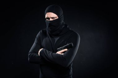 Thief in black balaclava holding gun in folded arms on black