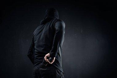 Thief hiding gun behind his back