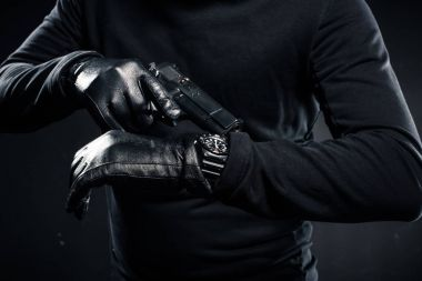 Man in gloves with gun checking his watch