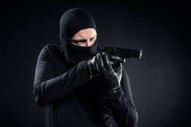 Burglar in balaclava aiming with gun on black