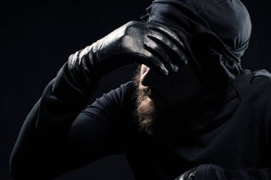 Robber in balaclava leaning his head on hand