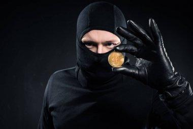 Man in black balaclava holding golden bitcoin stock vector