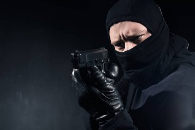 Robber in balaclava and gloves aiming with gun on black