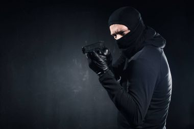 Male criminal in balaclava and gloves aiming with gun on black stock vector