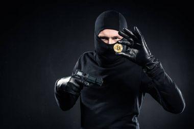 Man in black balaclava holding gun and golden bitcoin