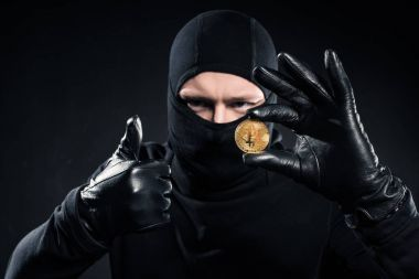 Man in black balaclava holding bitcoin and showing thumb up