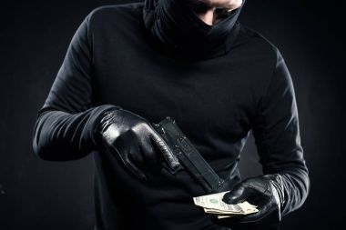 Man in black balaclava holding gun and dollars stock vector