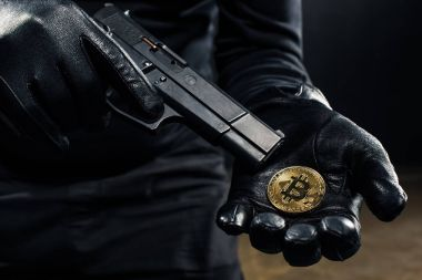 Close-up view of gun and bitcoin in hands of thief