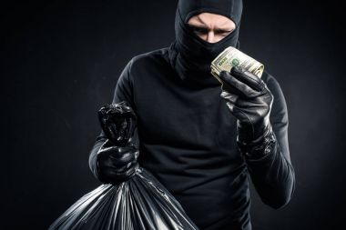 Man in balaclava holding plastic bag with cash and dollars