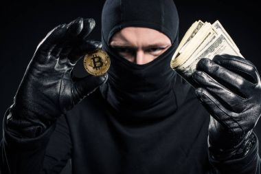 Male criminal in balaclava holding dollars and bitcoin