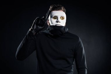 Thief in mask and bitcoins on eyes holding gun