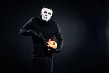 Burglar in mask holding gun and piggy bank stock vector