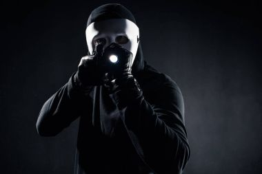 Burglar in mask and balaclava aiming with gun and flashlight