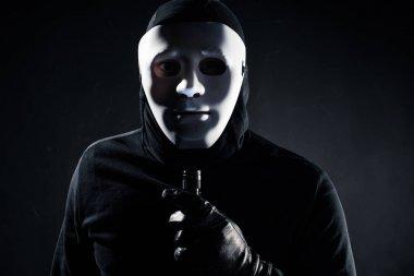 Robber in white mask holding flashlight