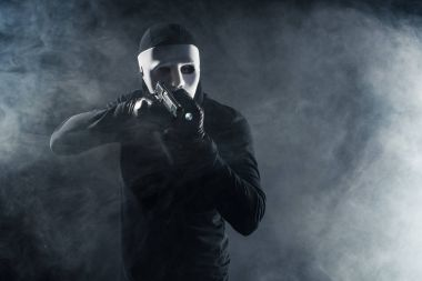 Man in mask and balaclava aiming with gun and flashlight