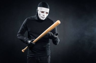 Criminal in mask and balaclava holding baseball bat