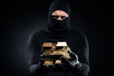 Man in balaclava holding gold bullions in his hands
